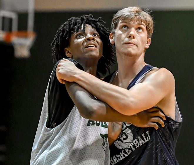 Aurora's Tavion Pride, left, and Hudson's Isaiah Powell work for position on a rebound during a boys basketball scrimmage.