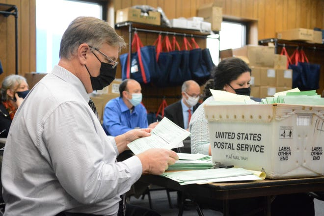 Election Bureau Director Albert L. Gricoski, left, opens provisional ballots alongside election bureau staff Christine Marmas, right, while poll watchers observe from behind at the Schuylkill County Election Bureau in Pottsville, Pa. on Nov. 10.