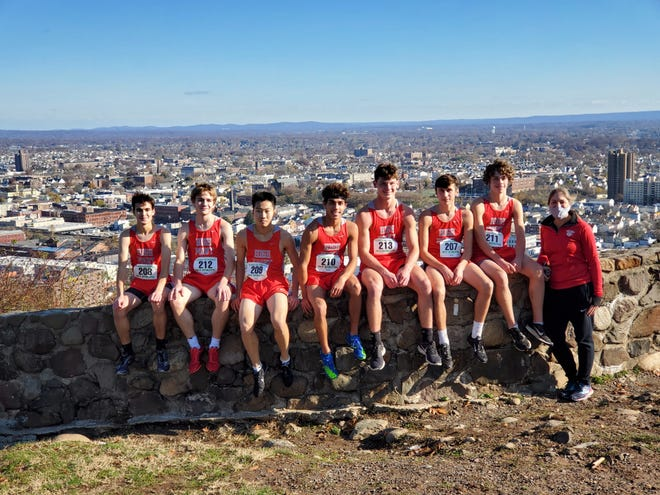 The High Point boys cross country team poses for a photo with head coach Lisabeth Sunda, far right, after placing fourth in the North 1, Group 2 race on Saturday at Garret Mountain.