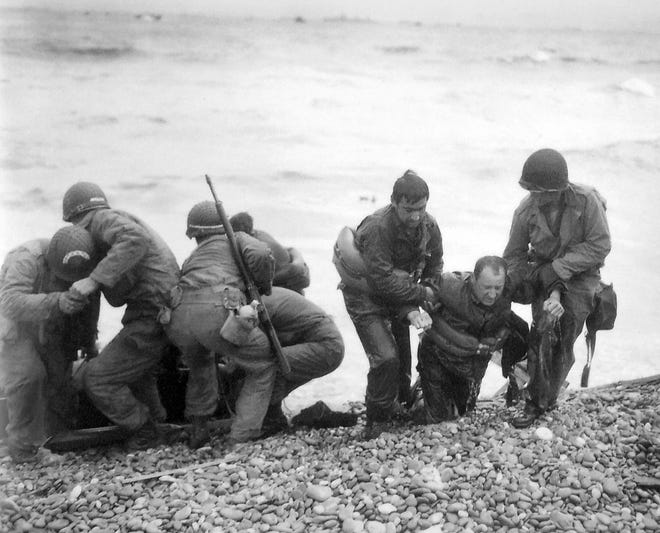 In this file photo from June 6, 1944, members of an American landing unit help their comrades ashore during the Normandy invasion. The men reached the zone code-named Utah Beach, near Sainte- Mere-Eglise, on a life raft after their landing craft was hit and sunk by German coastal defenses.
