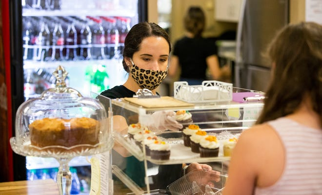 Lindsey Bennett, a server at the cafe inside Your Heart's Desire, grabs cupcakes for customers on Monday afternoon. The gift shop houses the cafe and Betty Cakes. Ocala was recently named the mid-size city with the most small businesses per capita in the country.
