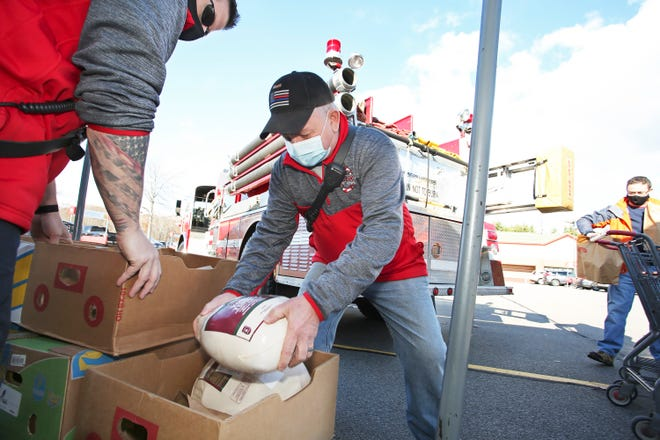 """Tony Pinder loads up turkeys as members of the York Village Fire Department join representatives from YCSA for the """"no hassle turkey drive"""" at Hannaford in York, Maine, on Saturday, Nov. 14, 2020, ahead of the Thanksgiving holiday."""
