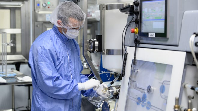 A Lonza Biologics employee in Portsmouth drains residual liquid from equipment used in the manufacture of the vaccine Moderna has developed against COVID-19 infections.