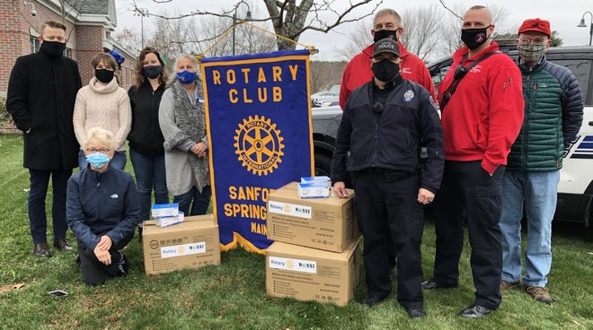Local Rotarians delivered face masks to the Sanford Police Department on Friday, Nov. 13, so that first-responders can distribute them throughout the community. Standing at left are Police Detective Eric Small, left, Sanford-Springvale Rotary Club Immediate Past President Diane Gerry, Rotary Club President Cassandra Mosher, and Rotary District 7780 Governor Peggy Belanger. Kneeling is Rotarian Kim LaChance. Standing at right are Police Officer Chris Cyr, front and left, Fire Captain Dwight Emmons, Firefighter Joe Wilber, and Rotarian and Past District Governor Lawrence Furbish. Missing from the photo, but present at the ceremony, is Rotarian Barbara Sutcliffe.