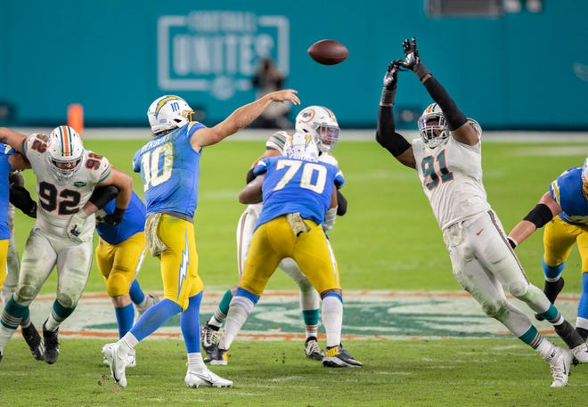 Chargers quarterback Justin Herbert is about to have his pass attempt tipped by Dolphins defensive end Emmanuel Ogbah (91) on a fourth-down play in the fourth quarter of Sunday's game at Hard Rock Stadium.