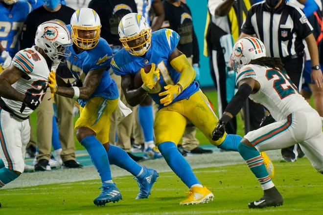 Chargers running back Kalen Ballage picks up some of his 68 yards against the Dolphins Sunday at Hard Rock Stadium.