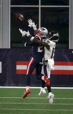 Foxboro, MA, Nov 15, 2020 - Patriot defender J.C. Jackson incepts a first half pass intended for Raven receiver Marquise Brown.  New England Patriots vs. the Baltimore Ravens at Gillette Stadium Sunday evening.    [The Providence Journal / Kris Craig]