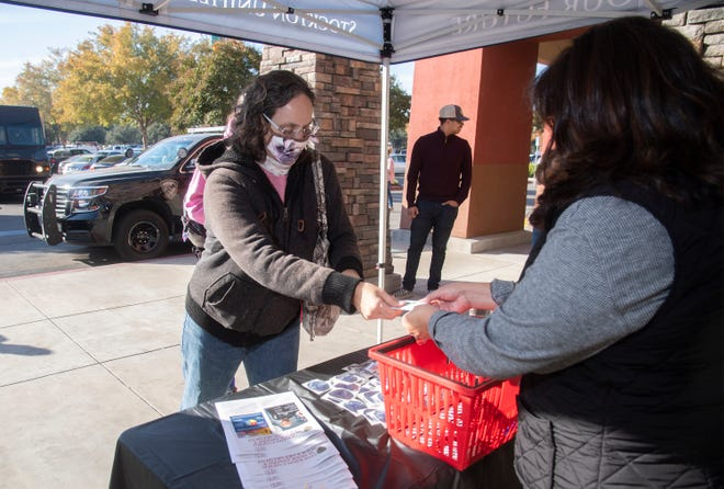 Laura Vanginkle, left, donates a meal/gift card to SUSD's Families in Transition's Esperanza Molina at the Friendsgiving Feast event in front of the Raley's supermarket on Morada Lane near Highway 99 in Stockton.