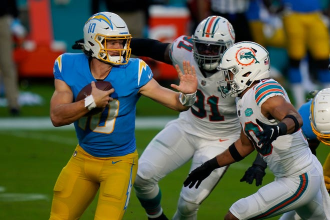 Los Angeles Chargers quarterback Justin Herbert tries to scramble away from Miami's Emmanuel Ogbah (91) and Nik Needham (40) during the first half of Sunday's game in Miami Gardens, Fla.