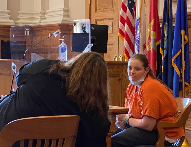 Lillian Cottrell talks with attorney Kristina Powers, of the Stark County Public Defender's Office, on Monday during a hearing in Stark County Common Pleas Court. Cottrell is scheduled to go on trial starting Dec. 1 on an endangering children charge stemming from allegations she padlocked a young girl in a dog cage as punishment.
