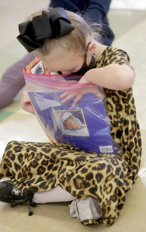 Walker Elementary kindergartener Layla Hyde explores a bag of newly donated books from the Scott and Edie Hamilton Foundation. The foundation donated the books to keep the more than 30-year tradition alive after the Canton Men's Club disbanded.