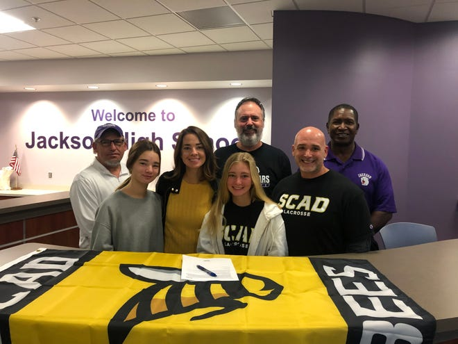 Annise Berkeley (middle) signed with the Savannah College of Art and Design, and is joined by (front, from left) coach Mahlon Downard, sister Kellen, mom Anna, father Matt,  (back row) head coach John Kroah, and coach Mike Peterson.