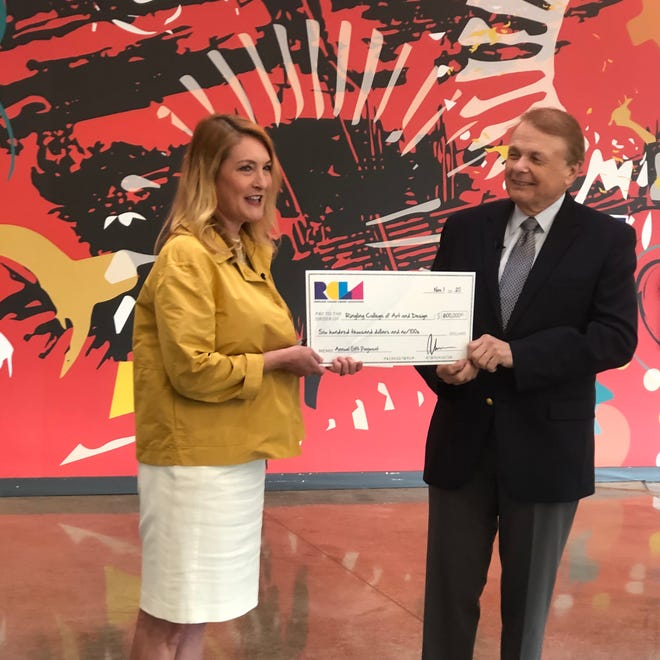 Ringling College Library Association President Emily Walsh presents a check to Ringling College President Larry Thompson.