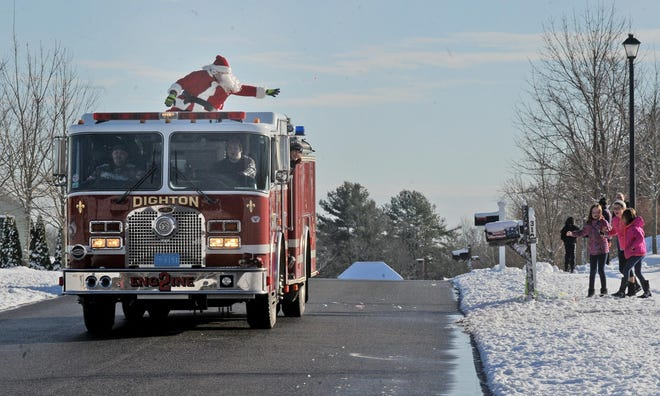 Santa Claus tosses candy to children as he visits town residents during the 2017 Santa Run.