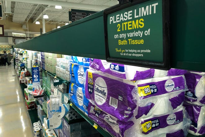 A sign tells customers that purchases of bath tissue are limited to two per customer at the Harris Teeter supermarket Monday.