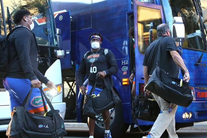 Florida players, including Jesiah Pierre (40), get off the team bus before Saturday's game against Arkansas at Ben Hill Griffin Stadium.