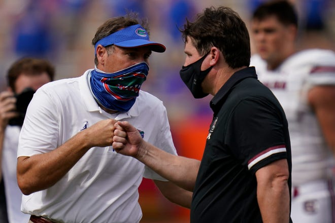 Florida head coach Dan Mullen, left, and South Carolina head coach Will Muschamp bump fists at the end of their game Oct. 3 in Gainesville.