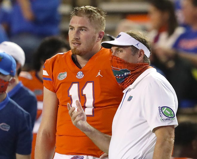 Florida coach Dan Mullen talks with quarterback Kyle Trask during Saturday's game against Arkansas at Ben Hill Griffin Stadium.