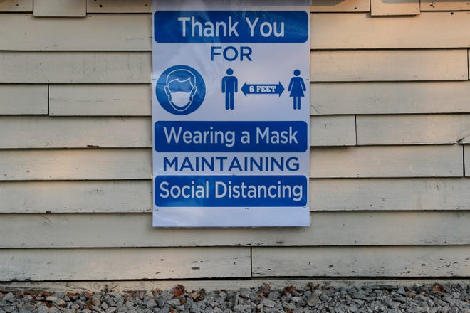 This sign shows mask wearing and social distancing guidelines.