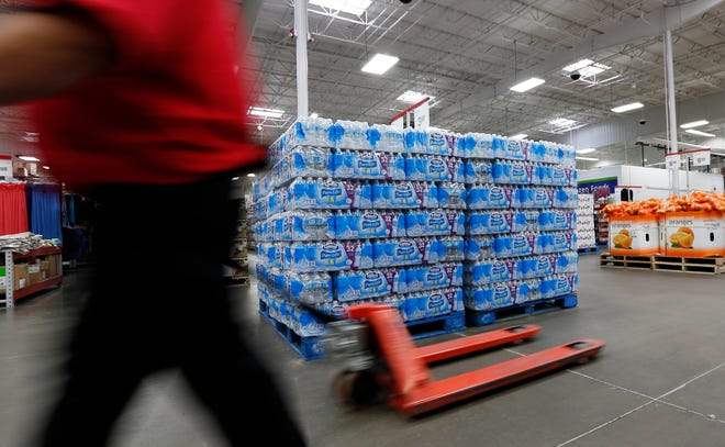 A customer walks past a bottled water display at a store.