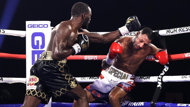 """Terrence """"Bud"""" Crawford, left, lands a blow to the head of Kell Brook, right, that leads to Crawford retaining his WBO welterweight title."""