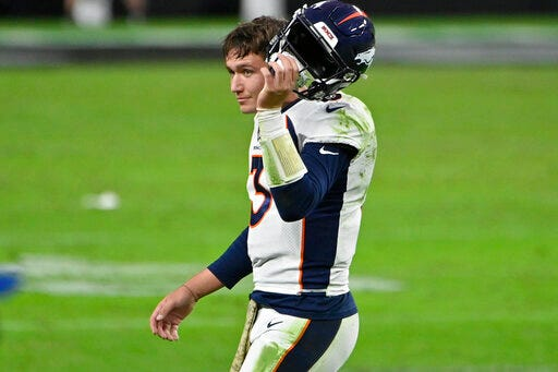 Denver Broncos quarterback Drew Lock takes off his  helmet after a play against the Las Vegas Raiders during the second half on Sunday in Las  Vegas. [AP photo/David Becker]