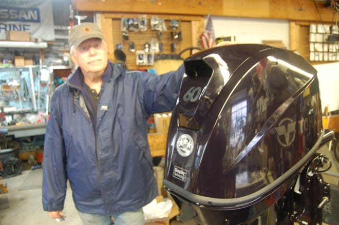 Jim Shields alongside a motor in his shop, Gander Marine, on Town Cove.