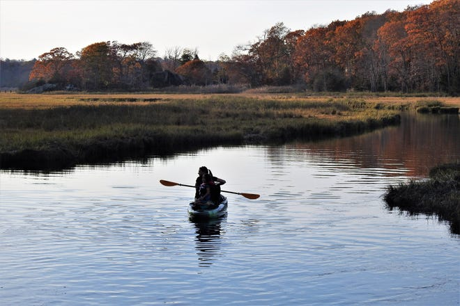 A kayaker moves through the water of the Gulf River in Scituate amid the stunning backdrop of fall foliage.