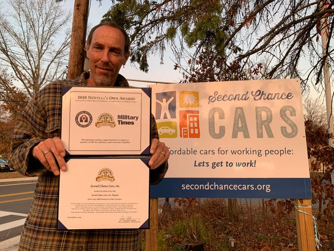 Second Chance Cars Executive Director Dan Holin of Concord holds the Newman's Own Award recently awarded to his non-profit.