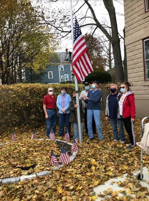 The board of the Stoneham Historical Society and Museum gathers on veterans day at the flagpole repaired by vocational students who saw it needed some attention.