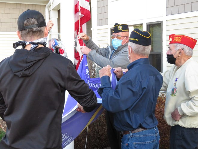 "Natick Veterans Services Officer Paul Carew, center, helps hoist a flag designating Natick as a ""Purple Heart Community"" during Veterans Day observances on Nov. 11."