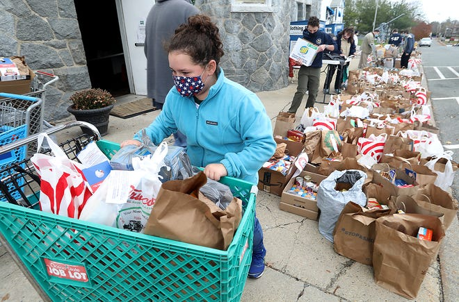 Lauren Rogers, 10, of Junior Girl Scout Troop 61944 pushes a loaded carriage of donated food while helping sort the donated food for the Rockland Food Pantry on Saturday, Nov. 14, 2020. They collected 8, 432 pounds of food.