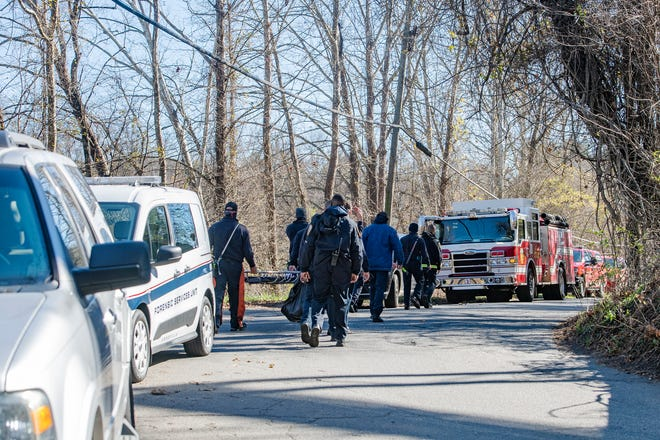 First responders return to their vehicles lining Emma Road at the railroad bridge as Asheville police investigate after a body was found the morning of Nov. 16, 2020 in the area near the French Broad River.