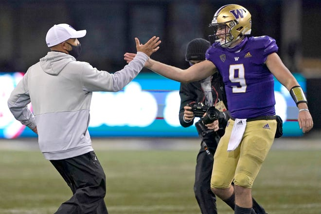 Washington head coach Jimmy Lake, left, greets starting quarterback Dylan Morris (9) after Washington beat Oregon State 27-21 in an NCAA college football game, Saturday, Nov. 14, 2020, in Seattle. The game was Lake's first since he was named head coach. (AP Photo/Ted S. Warren)