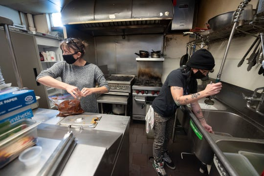 Bar manager Jen Rigley, left, and cook Amber Parent, clean up the kitchen at PJ's Lager House, in Detroit, November 16, 2020.  The bar is closing indefinitely due to new restrictions on indoor dining because of the increase in COVID-19 cases in the state. The Michigan Department of Health and Human Services on Sunday put another hold on indoor dining at bars and restaurants, and also ordered movie theaters, casinos and bowling alleys to close Wednesday through December 8.