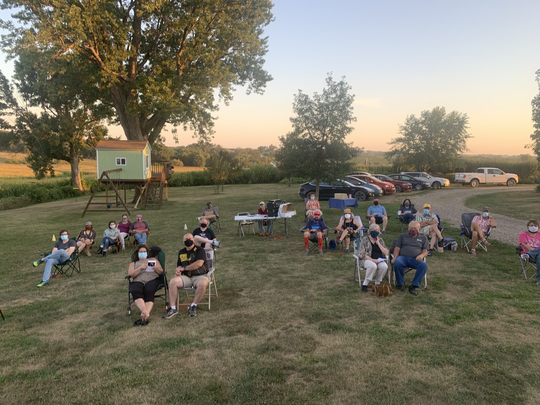 """A socially distanced audience members gather in socially distanced """"camps"""" in Trent Yoder's backyard during the summer of 2020 to watch """"Oscar."""" Yoder directed the production and built the set for the show. Audience """"camps"""" could be one to four people, spaced 10 feet apart. Masks were required."""