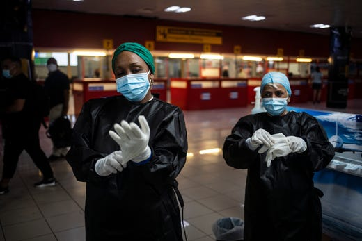Health workers prepare to take samples for a COVID-19 test from passengers who are arriving from Cancun Mexico, at the Jose Marti International Airport in Havana, Cuba, Sunday, Nov. 15, 2020. The airport is receiving its first commercial flights in over 8 months, since the country shut the facility down due to the coronavirus pandemic.