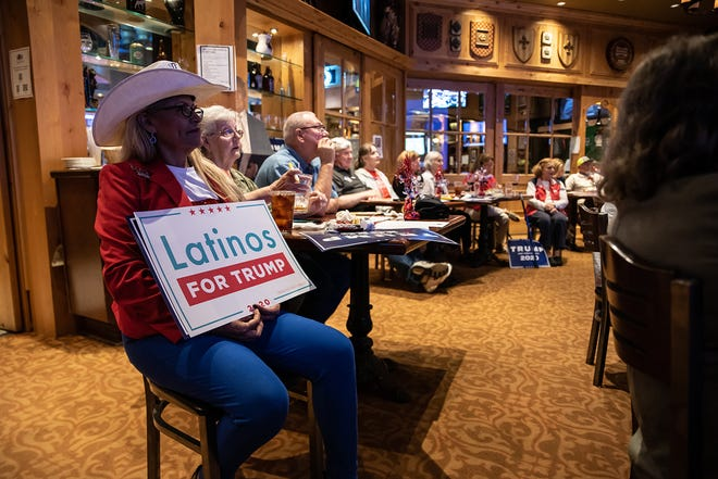 "A woman holds a ""Latinos for Trump"" sign at a watch party for the final presidential debate between President Donald Trump and former Vice President Joe Biden on October 22, 2020, in San Antonio, Texas."