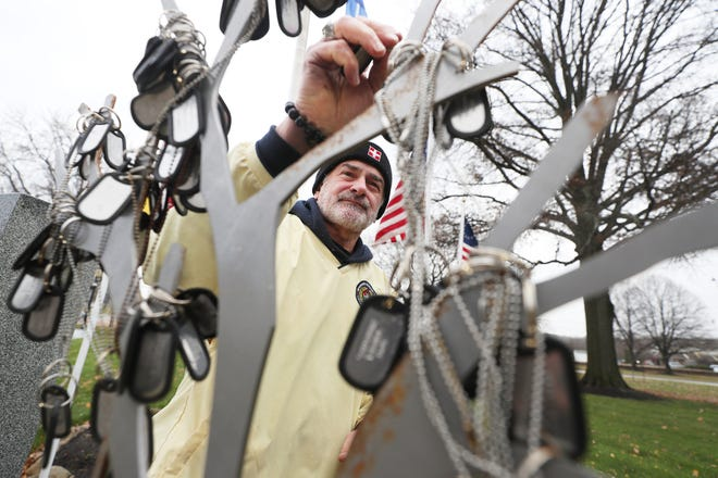 Silver Lake resident John Schluep, a Vietnam-era veteran of the U.S. Army, returns dog tags to the Warriors' Journey Home recovery tree Nov. 17, 2020, after picking them off the ground following a storm at the Tallmadge Veterans Memorial at Tallmadge Circle. [Mike Cardew/Beacon Journal]