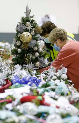 Mary Leuca, left, chairperson for Akron Children's Hospital Holiday Tree Festival, and Patty Hatrick, volunteer coordinator, set up a miniature tree this week that will go with a wreath at the John S. Knight Center in Akron. The event will be online this year.