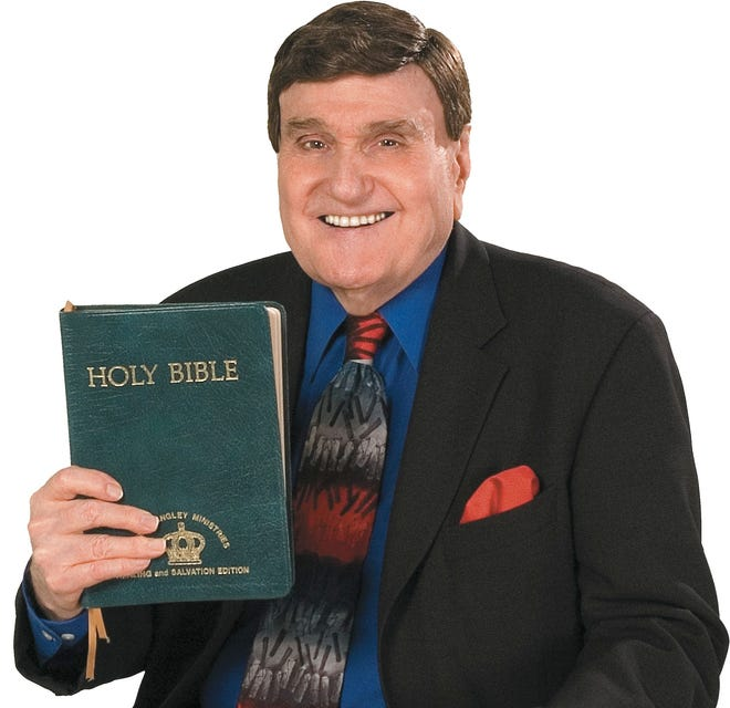 The Rev. Ernest Angley poses with a Bible in this undated file photo.