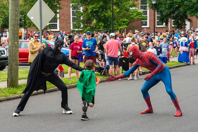Batman, left, and Spider-Man greet a young runner at last year's Doylestown 5K.