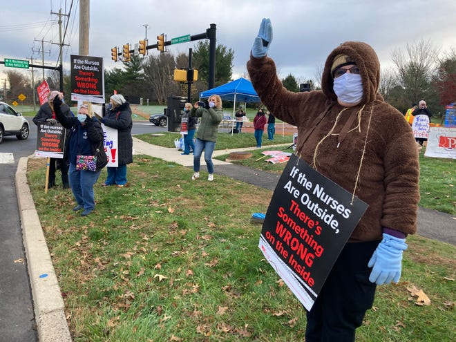 Anne DeMille, 60, a nurse at St. Mary Medical Center since 1979, waves to passing motorists who honked in support of striking nurses at the Middletown hospital. Staffing and wages are two big issues for the strike, which began on Tuesday, Nov. 17.