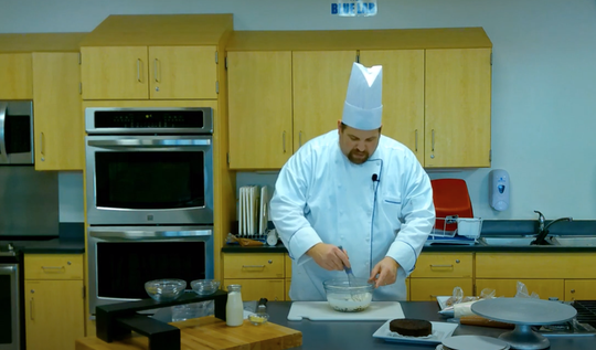 Christopher Polk has embraced technology and created youtube videos to demonstrate cooking for his students.