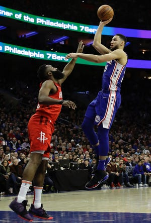 The Sixers' Ben Simmons shoots over the Rockets' James Harden.