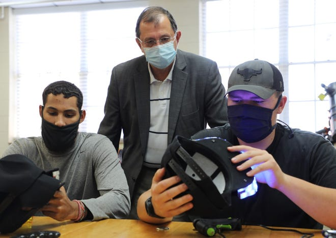 HPU's Talen Davis-Rentfro, Dr. Martin Mintchev and Jacob Bonner examine Aurakills prototypes.