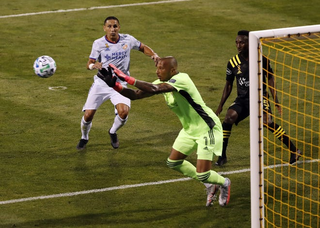Crew goalkeeper Eloy Room makes a save in front of defender Harrison Afful, right, and FC Cincinnati midfielder Adrien Regattin during a game at Mapfre Stadium on Sept. 6.