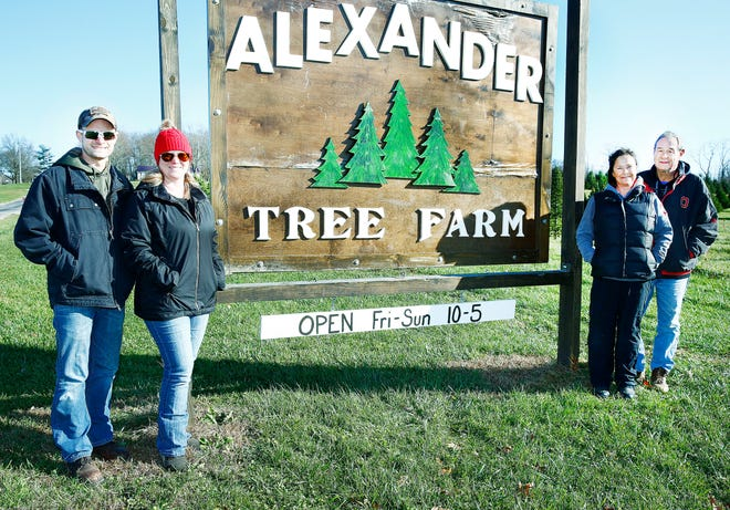 (From left to right) Alex and Michelle Perkins and Vickie and Al Holdren pose with the sign at the Alexander Tree Farm in Ashland. The tree farm opens for the season Nov. 20.