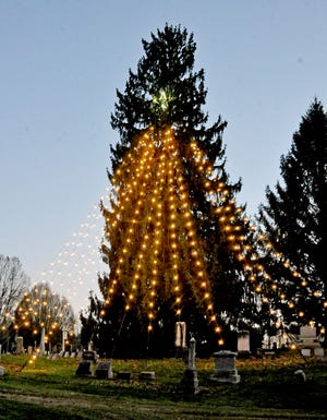 The community christmas tree stands tall in the cemetery for all to see.