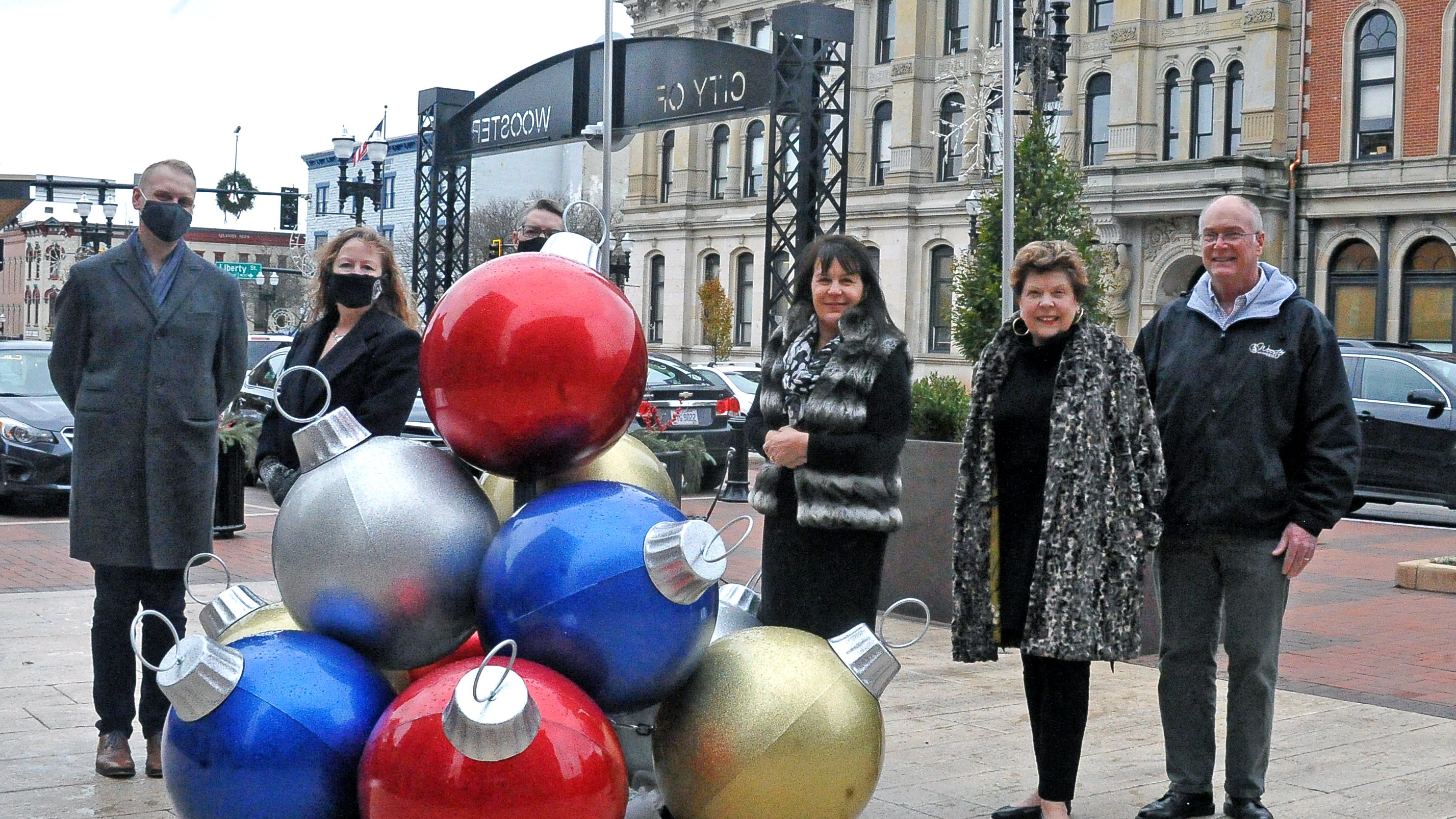 Standing by the newest holiday decoration on the square is John Benko-Scruggs, Shannon Waller, Joel Montgomery, Sue Williams, Sandra Hull and Wooster Mayor Bob Breneman. Waller and Benko-Scruggs worked to alter traditional events to follow coronavirus guidelines.